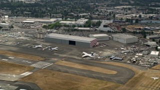 AX45_012 - 5K stock footage aerial video flying by airliners parked by a hangar at Boeing Field, Seattle, Washington, as a smaller plane lands