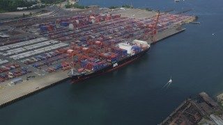 AX45_017 - 5K stock footage aerial video flying by a cargo ship loaded with containers docked at Port of Seattle, Washington