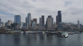 AX45_035 - 5K stock footage aerial video flying by skyscrapers and Central Waterfront piers in Downtown Seattle, Washington