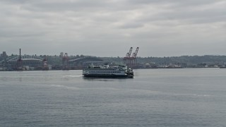 AX45_047 - 5K stock footage aerial video orbiting ferry sailing Elliott Bay, revealing Downtown Seattle skyline, Space Needle in the background, Washington