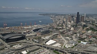 AX45_063 - 5K stock footage aerial video approaching Safeco and CenturyLink Fields, and pan toward skyscrapers in Downtown Seattle, Washington
