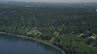 AX45_115 - 5K stock footage aerial video tilt from railroad tracks on the shore to reveal homes, Shoreline, Washington