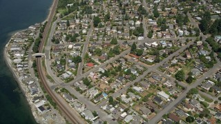 AX45_118 - 5K stock footage aerial video approach train tracks and a waterfront community, Shoreline, Washington