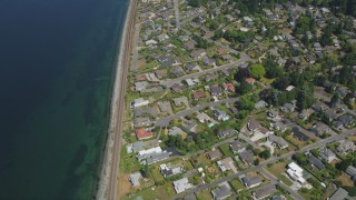 AX45_125 - 5K stock footage aerial video tilt from bird's eye of railroad tracks and waterfront suburban homes, Edmonds, Washington