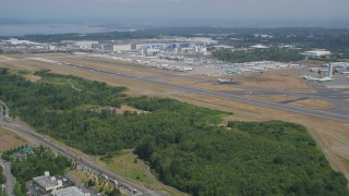 AX45_131 - 5K stock footage aerial video fly over trees to approach Paine Field and the Boeing Factory, Everett, Washington