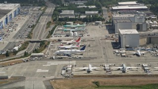 AX45_138 - 5K stock footage aerial video flyby airliners parked at Paine Field and reveal the Boeing Everett Factory, Washington
