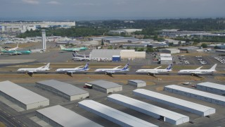 AX45_152 - 5K stock footage aerial video of panning across a row of six airliners at Paine Field, reveal Boeing Factory, Washington