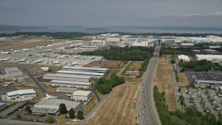 AX45_154 - 5K stock footage aerial video approach the Boeing Factory and pan to parked airliners, Paine Field, Washington