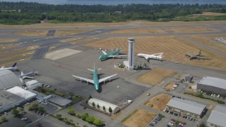 AX45_155 - 5K stock footage aerial video approach three airliners parked around an airport control tower, Paine Field, Washington