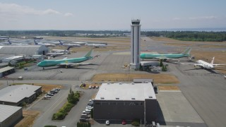 AX45_156 - 5K stock footage aerial video flyby three airplanes parked by the airport control tower, Paine Field, Washington