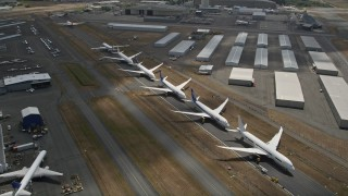AX46_003 - 5K stock footage aerial video approach and fly over a row of parked airliners, Paine Field, Washington