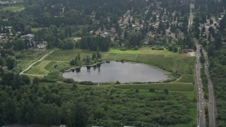 AX46_040 - 5K stock footage aerial video approaching Larsen Lake, surrounded by crop fields, Bellevue, Washington