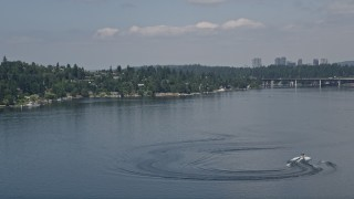 AX46_046 - 5K stock footage aerial video of tracking a speedboat pulling a raft on Lake Washington, Washington