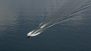 AX46_051 - 5K stock footage aerial video track a speedboat towing a raft across Lake Washington, Washington