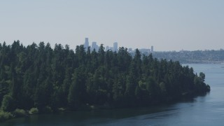 AX47_007 - 5K stock footage aerial video of Downtown Seattle skyline in the far distance beyond the tree-covered Bailey Peninsula, Washington