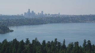 AX47_008 - 5K stock footage aerial video fly over trees on the Bailey Peninsula to reveal the Downtown Seattle skyline, Washington