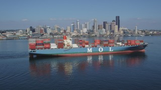 AX47_026 - 5K stock footage aerial video orbit a cargo ship sailing Elliott Bay with the skyline in the background, Downtown Seattle, Washington