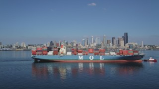 AX47_030 - 5K stock footage aerial video flyby a cargo ship and tugboat sailing Elliott Bay to focus on the Downtown Seattle skyline, Washington