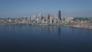 AX47_036 - 5K stock footage aerial video tilt up and approach the Seattle Waterfront and the Downtown Seattle skyline from Elliott Bay, Washington