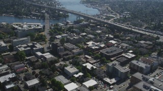 AX47_079 - 5K stock footage aerial video fly over an office building, tilt to reveal the bridge, Lake Union, and Downtown Seattle skyline in Washington