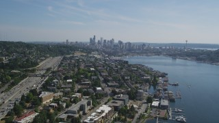 AX47_081 - 5K stock footage aerial video follow the shore of Lake Union to approach the Downtown Seattle skyline, Washington