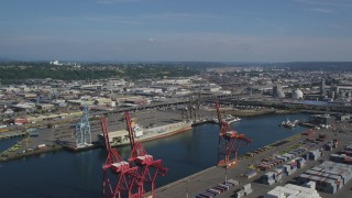 AX47_102 - 5K stock footage aerial video of cargo cranes and an empty cargo ship docked at Harbor Island, Seattle, Washington