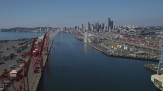AX47_103 - 5K stock footage aerial video flyby cranes and over the Duwamish Waterway at Harbor Island toward Downtown Seattle skyline, Washington