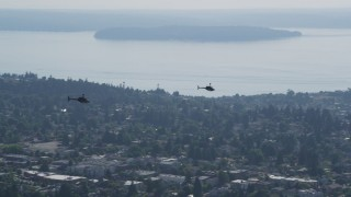 AX47_112 - 5K stock footage aerial video track a pair of Kiowa Warrior helicopters over residential neighborhoods, West Seattle, Washington