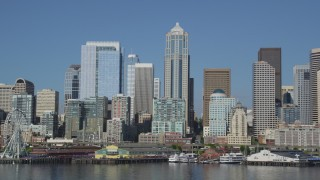AX47_124 - 5K stock footage aerial video of Seattle Great Wheel, Seattle Aquarium, and Waterfront piers below the Downtown Seattle skyline in Washington