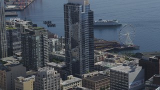 AX47_136 - 5K stock footage aerial video fly between downtown skyscrapers toward a ferry approaching the Central Waterfront, Downtown Seattle, Washington