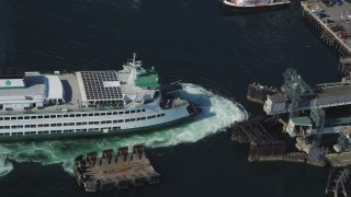 AX47_138 - 5K stock footage aerial video of bird's eye view of a ferry approaching the Seattle Ferry Terminal in Downtown Seattle, Washington
