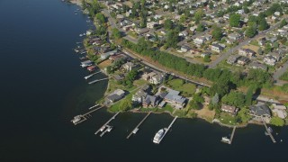 AX48_002 - 5K stock footage aerial video of approach lakeside homes and tilt to docks on Lake Washington in Kennydale, Renton, Washington