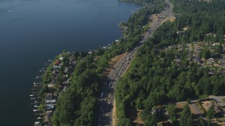 AX48_006 - 5K stock footage aerial video of flying over light traffic on I-405 and lakeside homes with docks, Bellevue, Washington