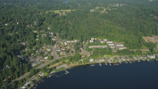 AX48_018 - 5K stock footage aerial video fly over lakefront homes with docks and trees to approach rural homes, Sammamish, Washington