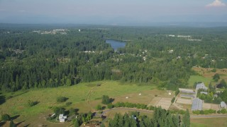 AX48_019 - 5K stock footage aerial video fly over rural homes and equestrian center to approach lakeside homes, Sammamish, Washington