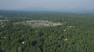 AX48_022 - 5K stock footage aerial video fly over lush green trees to approach a small residential neighborhood, Sammamish, Washington