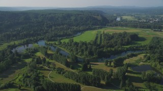 AX48_029 - 5K stock footage aerial video fly over a fork in the Snoqualmie River to approach a green field in Carnation, Washington