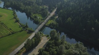 AX48_030 - 5K stock footage aerial video fly over a green field to approach a small bridge spanning the Snoqualmie River in Carnation, Washington