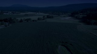 AX48_040_DFN - Aerial stock footage of Day for night color corrected aerial footage of crop fields and a country road near a greenhouse in Carnation, Washington