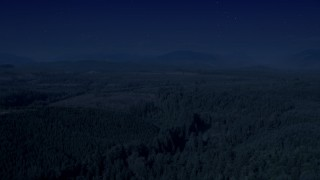 AX48_046_DFN - Aerial stock footage of 4K day for night color corrected aerial footage of a vast evergreen forest, and approach a clear cut area in King County, Washington