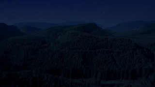 AX48_053_DFN - Aerial stock footage of Day for night color corrected aerial footage of flying over a wooded mountain in King County, Seattle, Washington