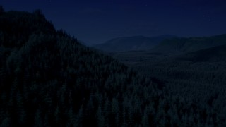 AX48_054_DFN - Aerial stock footage of 4K day for night color corrected aerial footage of flying over wooded mountain slope toward a clear cut area, King County, Washington