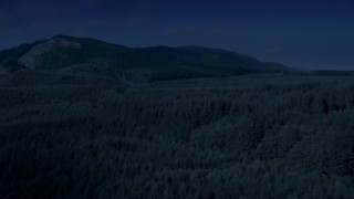 AX48_058_DFN - Aerial stock footage of Day for night color corrected aerial footage of evergreen forest, reveal the South Fork Tolt Reservoir, Cascade Range, Washington