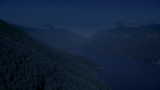 AX48_059_DFN - Aerial stock footage of 4K day for night color corrected aerial footage of evergreen trees on mountain slope next to the South Fork Tolt Reservoir, Cascade Range, Washington