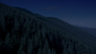 AX48_060_DFN - Aerial stock footage of Day for night color corrected aerial footage of mountain slopes covered with evergreen trees in the Cascade Range, Washington