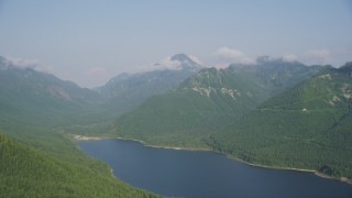 AX48_061 - 5K stock footage aerial video of wooded mountain peaks beside the South Fork Tolt Reservoir, Cascade Range, Washington