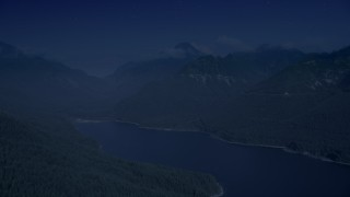 AX48_061_DFN - Aerial stock footage of 4K day for night color corrected aerial footage of wooded mountain peaks beside the South Fork Tolt Reservoir, Cascade Range, Washington