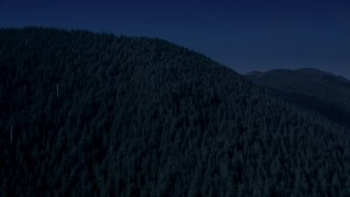 AX48_062_DFN - Aerial stock footage of 4K day for night color corrected aerial footage of evergreen trees covering a mountain ridge in the Cascade Range, Washington
