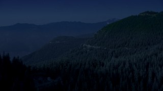 AX48_063_DFN - Aerial stock footage of Day for night color corrected aerial footage of a mountain ridge and evergreen trees on mountain slopes, Cascade Range, Washington