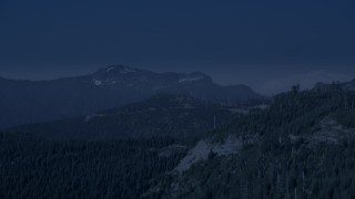 AX48_064_DFN - Aerial stock footage of 4K day for night color corrected aerial footage of evergreen trees on the slope of a mountain ridge in the Cascade Range, Washington